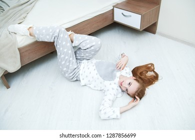 An attractive young girl is doing exercises in a pajamas lying on the floor near the bed at home. Beauty, cosmetics.