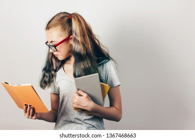 Attractive young girl with glasses reading a book. Grey wall on background, copy space. Back to school concept.