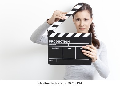 Attractive young girl holding clapper board front of her face.
