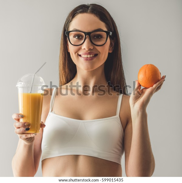 Attractive young girl is holding a glass of juice and an orange, looking at camera and smiling, on gray background