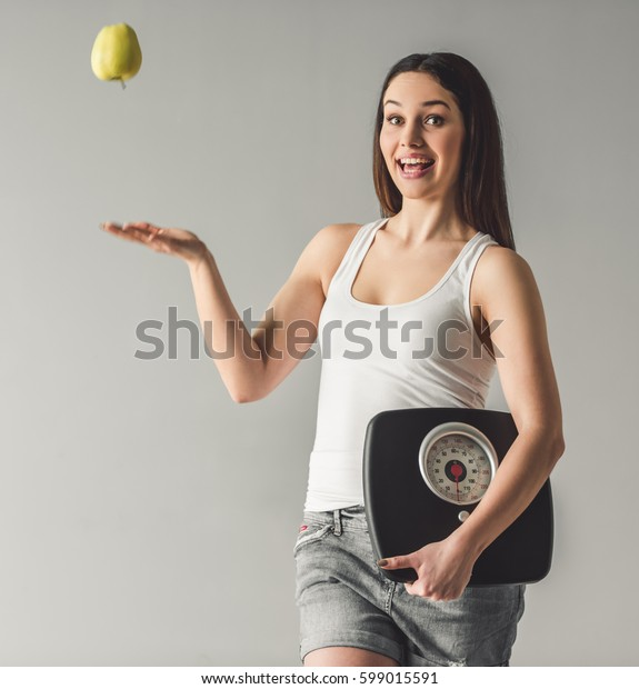 Attractive young girl is holding weigh scales, tossing an apple, looking at camera and smiling, on gray background