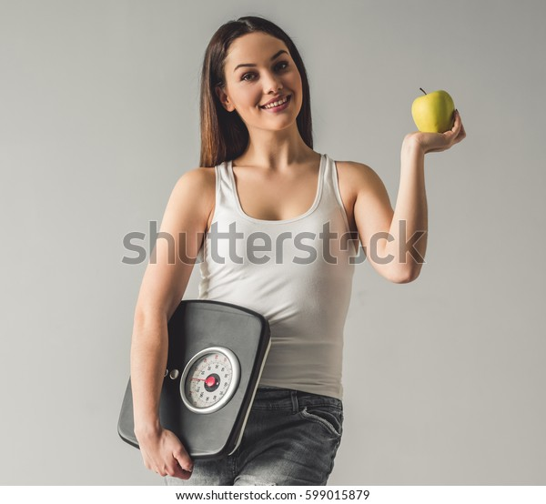 Attractive young girl is holding weigh scales and an apple, looking at camera and smiling, on gray background