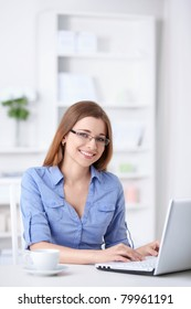 Attractive young girl with a laptop at home