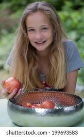 Attractive young girl with long blond hair and a lovely friendly smile sitting at a garden table in front of a bowl of fresh red apples holding one in her hand