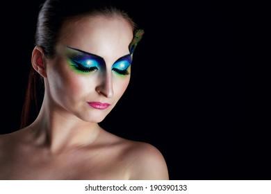 Attractive young girl with makeup peacock bird closeup portrait