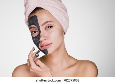 an attractive young girl with a pink towel on her head applied a clay useful mask to half the face