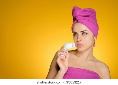 attractive young girl with a pink towel on her head doing face cleansing with a special brush