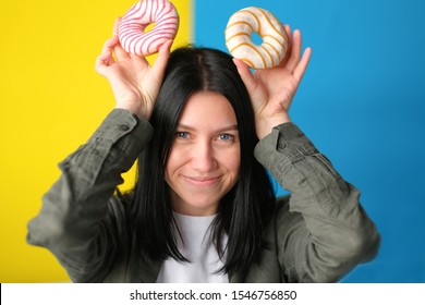 Attractive young girl posing with two donuts in her hands on a yellow-blue background. donuts like mickey mouse ears