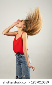 attractive young girl in red shirt and jean , with flying long hair , making face on white background . happy concept
