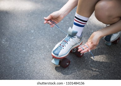 Attractive young girl rides on the stylish quad skates in the street in a park among green trees on the road. She performs disco dance on roller skates, listens to music, has fun and enjoy