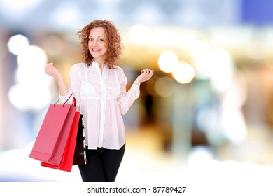 attractive young girl with shopping bags in front of the shop