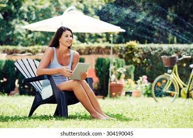 Attractive young girl sitting in the garden with her digital tablet