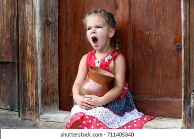 Attractive young girl sitting on the threshold of countryside house and holding an earthenware pot with organic milk, she is tired and yawning, summer outdoor, healthy lifestyle concept