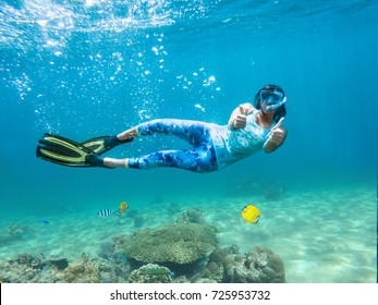 Attractive young girl snorkeling under water holding thumbs up.