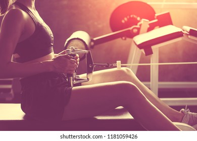 Attractive young girl in sport wear working out with fitness equipment in a professional gym. Confident young woman in fitness center. Training in gym, being fit and firm,  sport concept.