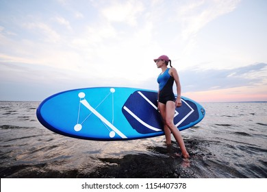 attractive young girl with sup board on the background of the sea and sunset