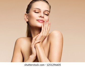 Attractive young girl touching her lips. Photo of girl with perfect skin on beige background. Beauty & Skin care concept