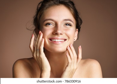 Attractive young girl touching her face on beige background. Beauty & Skin care concept