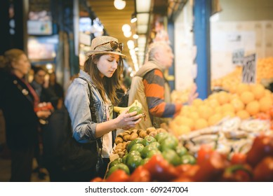 Attractive young girl traveler, buying fresh fruit at the sunday market