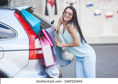 Attractive young girl trying to put a lot of retails into a car. Woman putting shopping bags into a luggage. Young female shoving up her shopping bags into a trunk.
