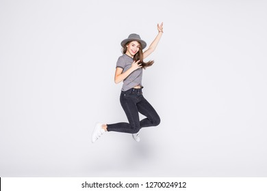 Attractive young girl wearing casual flying in air isolated over grey background