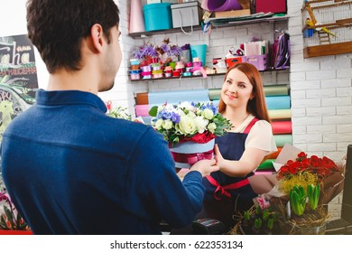attractive young girl working in a flower shop. A man buys flowers from florists. flower shop