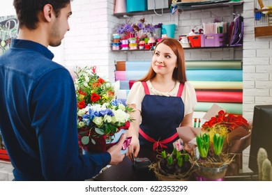 attractive young girl working in a flower shop.A man buys flowers from florists. flower shop