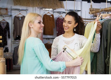 Attractive young girls choosing cloths in shop