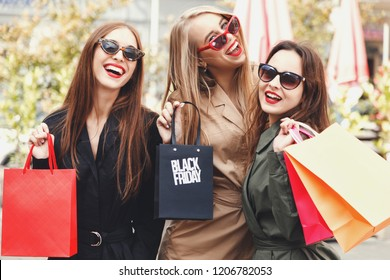 Attractive young girls wearing trench-coat and sunglasses laughing with colorful shopping bags at shopping mall background during shopping process, concept of consumerism, sale, rich life