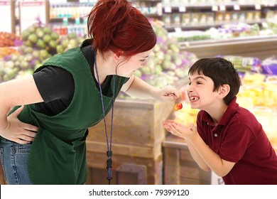 Attractive young grocery clerk sharing fresh cherries with child customer in grocery store.
