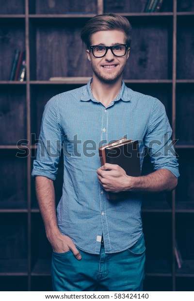 An attractive young guy in glasses standing in front of shelves,  holding books and keeping his hand in a pocket