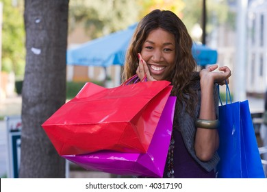 Attractive young happy African American woman walking in an urban city environment and carrying shopping bags.