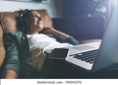Attractive young happy woman listening to music in headphones with pleasure at coworking office, lying on sofa, using laptop and mobile phone and resting.