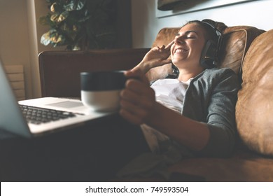 Attractive young happy woman listening to music in headphones with pleasure at coworking office, lying on sofa, using laptop, drinking hot coffee from nice cup and resting.