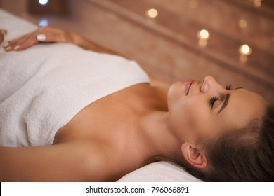 Attractive young happy woman lying on the massage table smiling with her eyes closed relaxing at the spa hotel resort wellness beauty sensuality femininity body skin care health harmony