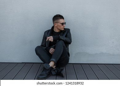 Attractive young hipster man in black sunglasses, black jacket, black sneakers and trendy jeans sitting on a wooden floor near a gray wall. Handsome fashionable modern guy