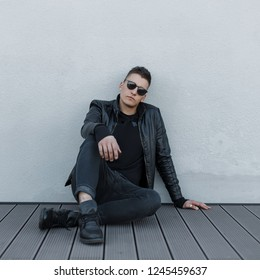 Attractive young hipster man in black sunglasses, black jacket, stylish sweatshirt and trendy jeans, rest and sits on a wooden floor outdoors near a gray wall. Fashionable modern guy