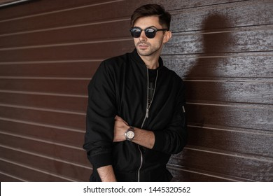 Attractive young hipster man with stylish hairstyle in fashionable black clothes in trendy dark sunglasses is resting near a brown vintage wooden wall in the street. Urban guy. American style.