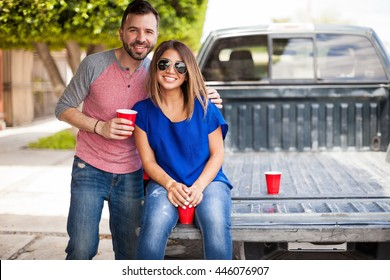 Attractive young Hispanic couple seated in the back of a pick up truck and drinking beer outdoors