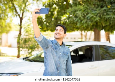 Attractive young hispanic man taking selfie with his brand new car in background