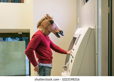 attractive young horse man takes money from the ATM