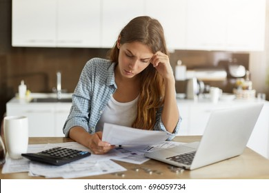 Attractive young housewife wearing shirt at home studying gas and electricity bills, checking calculations, looking at sheet of paper in her hands with serious and focused expression on her face