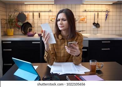 Atraktivní mladá žena v domácnosti nosí košili doma a zkoumá účty za plyn a elektřinu. hrozně zvažuje výdaje tento měsíc a je při kontrole účtů pod stresem.