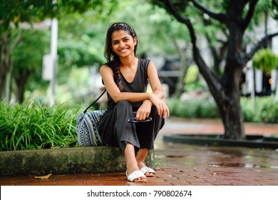 Attractive and young Indian Asian woman (tourist) sitting in the shade under trees on the curb. She is smiling at the camera while she holds a pair of sunglasses.