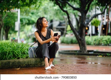 Attractive and young Indian Asian woman (tourist) sitting in the shade under trees on the curb. She's checking her phone and looking away.
