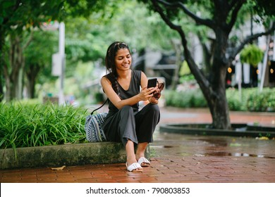 Attractive and young Indian Asian woman (tourist) sitting in the shade under trees on the curb. She's smiling as she checks her smartphone.