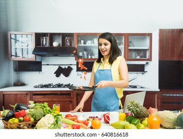 Attractive young Indian girl wearing apron in kitchen and tossing vegetables in frying pan, with table full of fruits and vegetables and computer