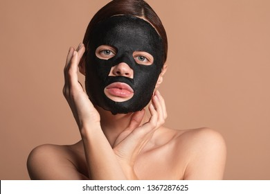 Attractive young lady with bare shoulders standing isolated on the beige background with a natural black sheet mask on her face