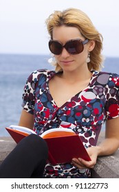 Attractive young lady reading a book by the sea.