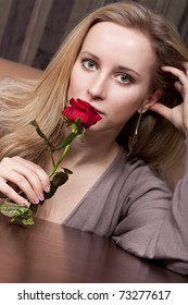 Attractive young lady with a red rose